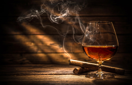 54094133 - glass of whiskey with smoking cigar and ice cubes on wooden table